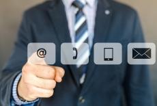 mężczyzna wskazuje na ekranie symbole e-mail, słuchawka telefoniczna, telefon komórkowy, koperta