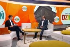 Zdjęcie ze studia telewizyjnego. Prezenter telewizyjny siedzi na przeciwko Dyrektora Federczka.
